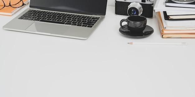 Minimaler fotografarbeitsplatz mit laptop und bürozubehör