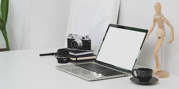 Minimaler fotografarbeitsplatz mit offenem laptop des leeren bildschirms