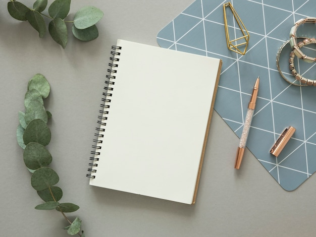 Minimaler frauenarbeitsschreibtischmodell. geöffnetes spiralblock mit kopierraum, goldbriefpapier und eukalyptuszweig. flach liegen