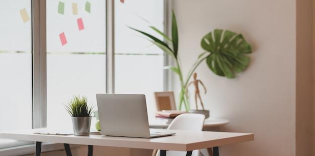 Minimaler grafikdesignerarbeitsplatz mit offener laptop-computer