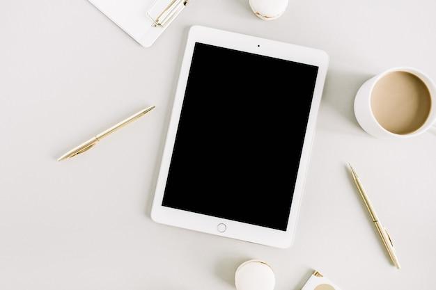Minimaler home-office-arbeitsplatz mit tablet, makronen, kaffeetasse auf pastellfarbenem hintergrund. flache lage, ansicht von oben