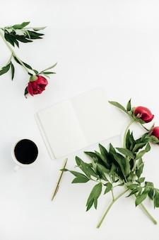Minimaler home-office-schreibtisch mit leerem notizbuch, kaffee und pfingstrosenblumen auf weißem hintergrund. flache lage, ansicht von oben