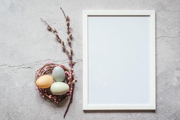 Minimaler osterhintergrund mit weißem bilderrahmen, ostereiern im vogelnest und weidenkätzchenzweigen.