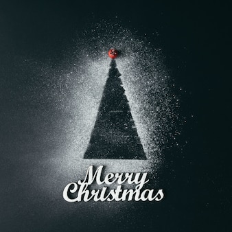 Minimaler weihnachtsbaum mit zuckerschnee auf dunkler oberfläche