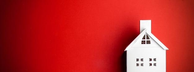 Minimaler weihnachtshintergrund mit einem weißen dekorativen haus auf rotem hintergrund. minimales konzept.