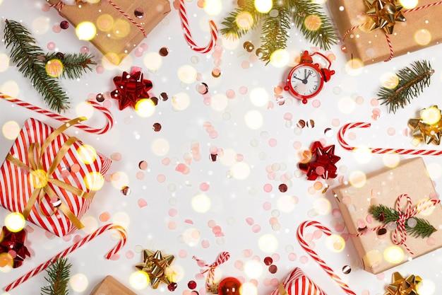 Minimaler weihnachtsrahmen mit geschenkbox, papierdekorationen, fichtenzweigen und zuckerstange auf weißem hintergrund. neujahrsfeiertagshintergrund. flache lage, draufsicht, rahmen