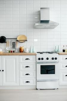 Minimaler weißer kücheninnenraum mit pflanze auf hölzernen arbeitsplatten.