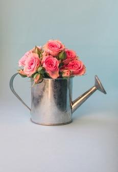 Minimales blumenbild mit minigießkanne und rosa rosen gegen pastellblau