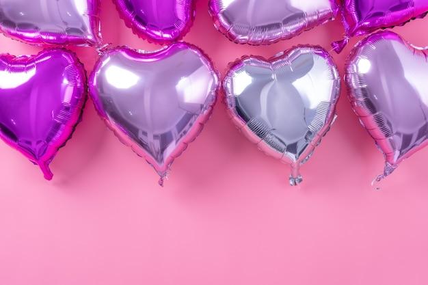 Minimales designkonzept des valentinstags - schöner realer herzformfolienballon lokalisiert auf hellrosa hintergrund