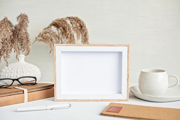 Minimales desktop-modell mit stationärer bio-farbe, kaffeetasse und rahmen