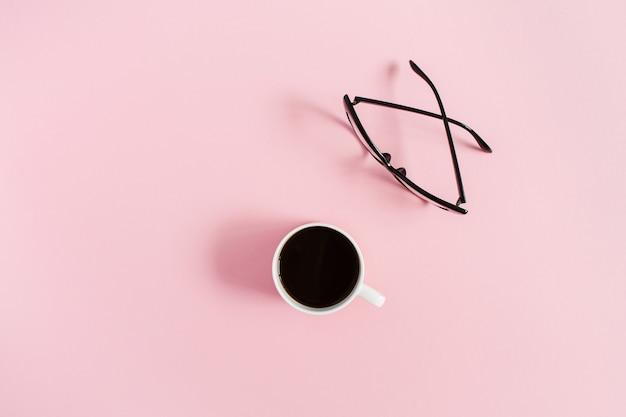 Minimales frauen-desktop-konzept mit kaffeetasse und gläsern auf rosa