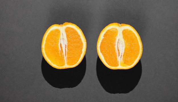 Minimales fruchtkonzept. zwei orangenhälften auf schwarzem hintergrund. draufsicht.