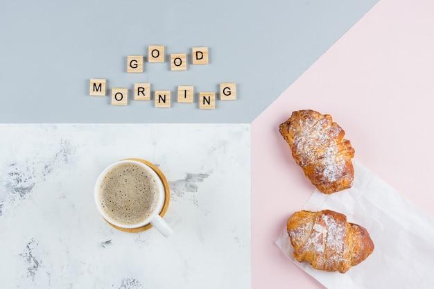 Minimales konzept des frühstücks des gutenmorgens. tasse kaffee, croissant und text guten morgen, flach zu legen