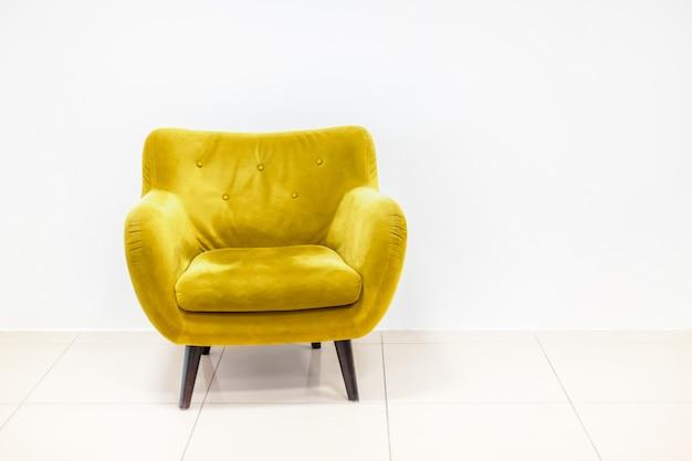 Minimales konzept des wohninnenraums mit hellem goldgelbem farbsessel auf weißem boden und hintergrund. wandmodell im skandinavischen stil.