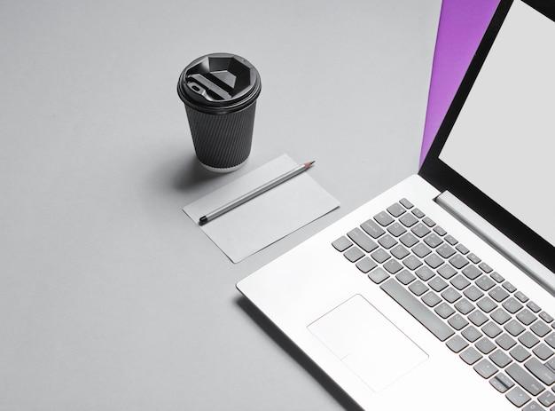 Minimales konzept für den arbeitsbereich. notizbuch, blatt papier mit einem bleistift, pappbehälter des kaffees auf lila grauem tisch