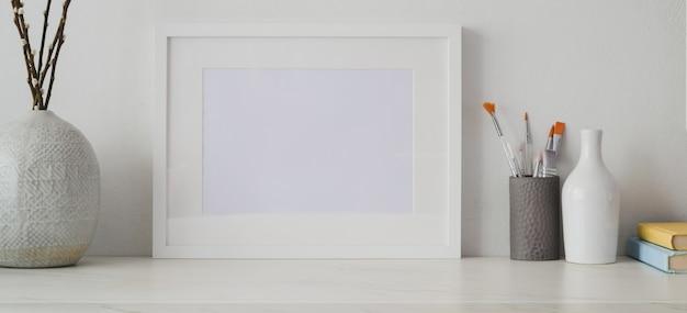 Minimales künstlerstudio mit leerem fotorahmen und büroartikel auf weißem schreibtisch und weißer wand