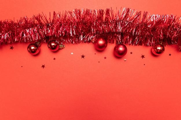 Minimales neues jahr. weihnachtszusammensetzung mit weihnachtslametta auf pastellrot.