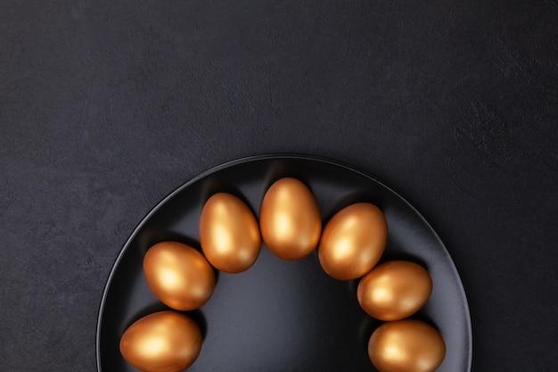 Minimales osterkonzept. stilvolle goldene verzierte ostereier auf schwarzem teller lokalisiert auf schwarzem marmorhintergrund