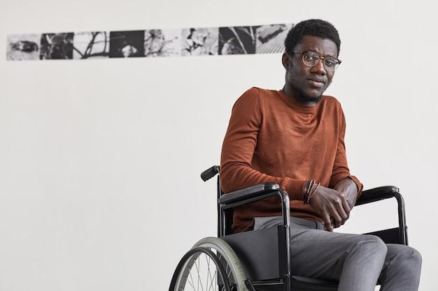 Minimales porträt des jungen afroamerikanischen mannes, der rollstuhl benutzt und gegen weiße wand in der galerie der modernen kunst aufwirft,