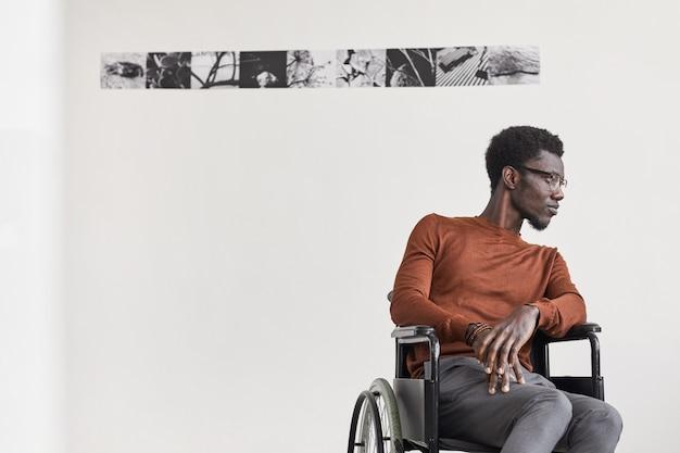 Minimales porträt des jungen afroamerikanischen mannes, der rollstuhl benutzt und weg schaut, während er in der galerie der modernen kunst aufwirft,