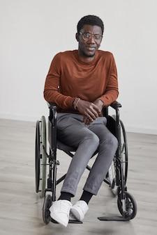 Minimales porträt des jungen afroamerikanischen mannes in voller länge, der rollstuhl benutzt und gegen weiße wand aufwirft