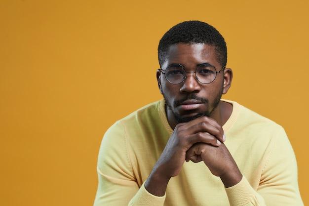 Minimales porträt eines afroamerikanischen mannes mit brille und blick in die kamera, während er das kinn auf ...