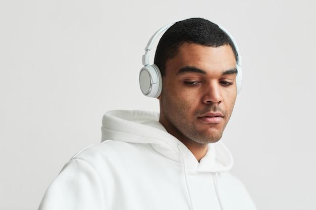 Minimales porträt eines jungen lateinamerikanischen mannes mit kopfhörern und weißem hoodie beim musikhören, kopierraum