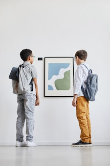 Minimales porträt in voller länge von zwei schuljungen, die abstrakte gemälde in der galerie für moderne kunst betrachten, kopierraum