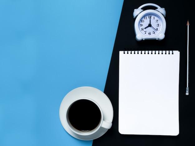 Minimales schwarzes arbeitsplatzkonzept: notizblock, bleistift, wecker, kaffee, draufsicht.