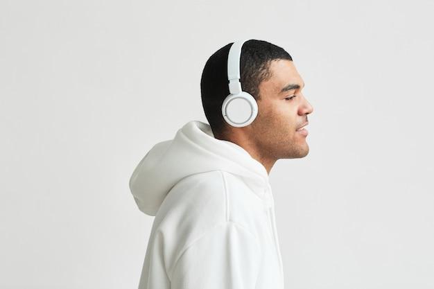 Minimales seitenansichtporträt eines modernen lateinamerikanischen mannes, der einen weißen hoodie mit kopfhörern trägt, während er musik hört, raum kopieren