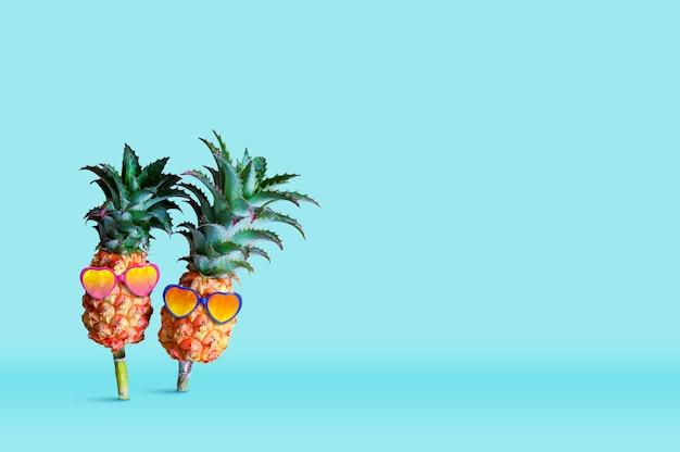 Minimales sommerkonzeptdesign der tragenden sonnenbrille der ananas auf blauem hintergrund
