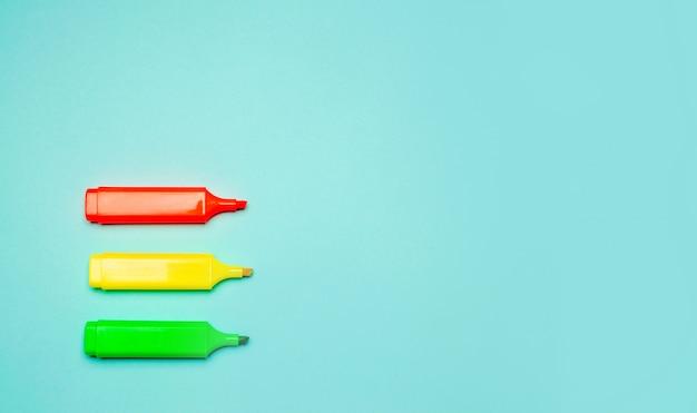 Minimalismus. drei mehrfarbige markierungen auf blauem grund. kreativität, pin up, schule st