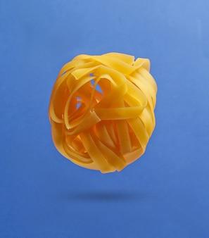 Minimalismus italienisches lebensmittelkonzept. rohe tagliatelle-nudeln auf blauem hintergrund. 3d-foto mit schatten