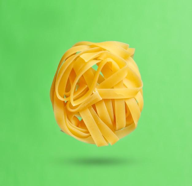 Minimalismus italienisches lebensmittelkonzept. rohe tagliatelle-nudeln auf grünem hintergrund. 3d-foto mit schatten