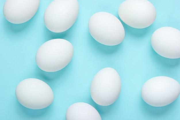 Minimalismus lebensmittelkonzept. viele eier auf einem blauen tisch. draufsicht