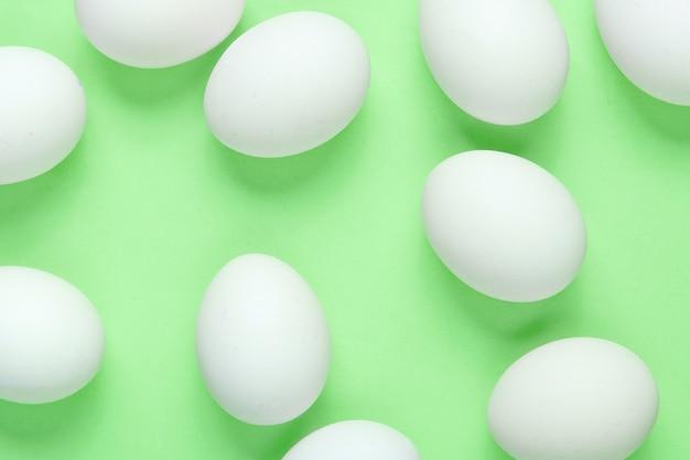Minimalismus lebensmittelkonzept. viele eier auf grünem hintergrund. draufsicht