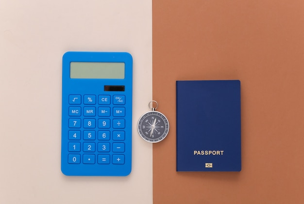 Minimalismus reisen flach. kompass, taschenrechner und reisepass auf beige braunem hintergrund. ansicht von oben