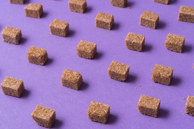 Minimalismus-stil. brown-zuckerwürfel gegen purpur.