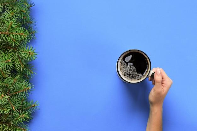 Minimalistic-artfrauenhand, die einen becher kaffee auf purpur hält. flachgelegt, draufsicht