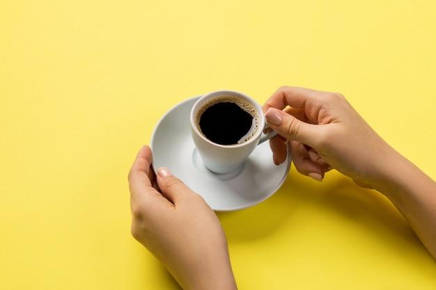 Minimalistic-artfrauenhand, die einen tasse kaffee auf gelb hält