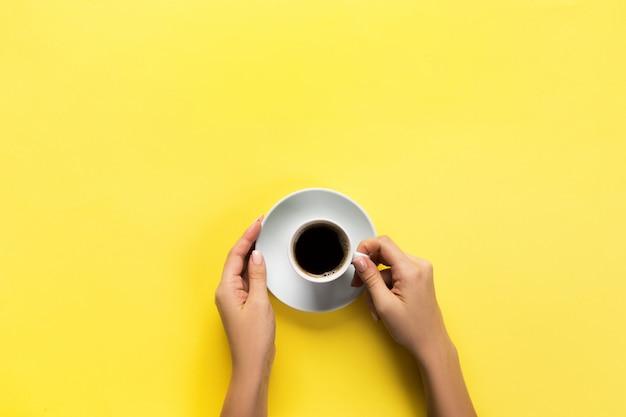 Minimalistic-artfrauenhand, die einen tasse kaffee auf gelbem hintergrund hält. flachgelegt, draufsicht