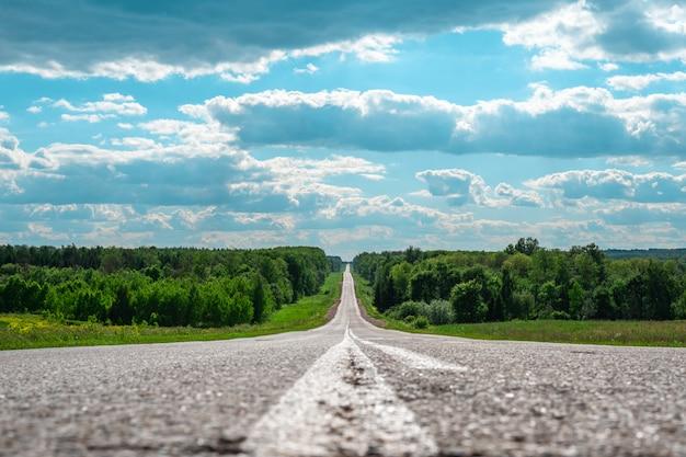 Minimalistic-landschaft der asphaltstraße in den sprüngen des entfernten horizontes