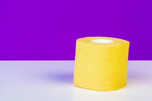 Minimalistic-zusammensetzung des hellen gelben toilettenpapiers rollt auf purpur