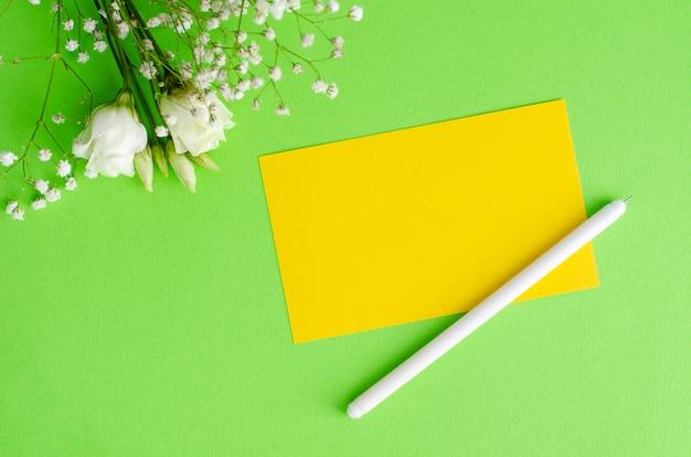 Minimalistic-zusammensetzung mit einer gelben leeren karte, einem stift und blumen auf grünem hintergrund. flay lag, mockup-konzept.
