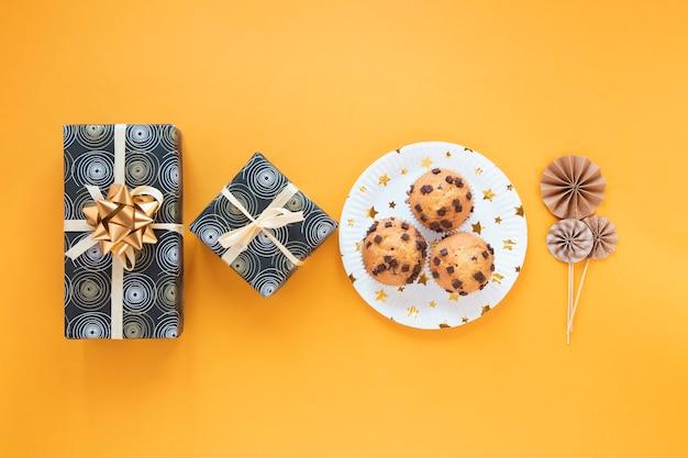 Minimalistische anordnung mit geburtstagsgeschenken und kleinen kuchen