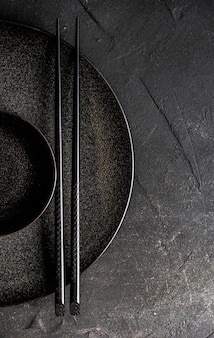 Minimalistische asiatische tischdekoration mit schwarzen schalen und essstäbchen auf schwarzem betontisch