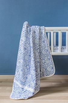 Minimalistische babyausstattung mit einem eleganten, kleinen, schicken, rosafarbenen stuhl, einer verzierten leiter und einem kinderbett