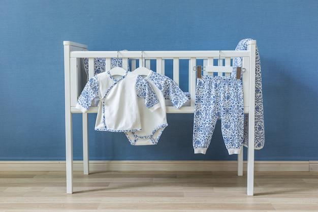 Minimalistische babyausstattung mit einem eleganten kleinen stuhl, einer dekorierten leiter und einem kinderbett
