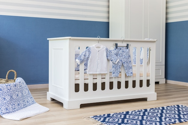 Minimalistische babyausstattung mit elegantem, kleinem, schickem stuhl und dekorierter leiter