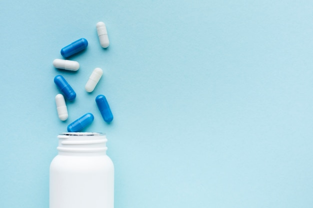 Minimalistische blaue und weiße pillen mit plastikflasche